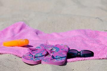 Badelatschen auf dem Handtuch am Sandstrand