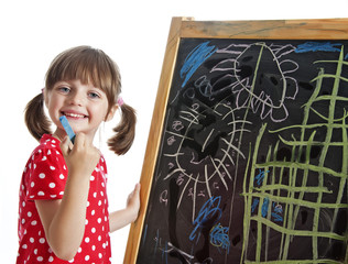 little girl drawing picture with chalks on a black board
