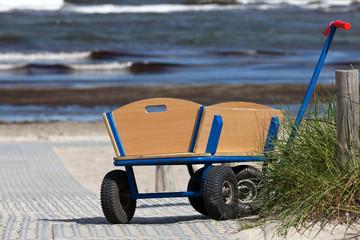 Bollerwagen steht allein am Wegesrand zum Strand