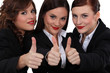 Three businesswomen giving the thumb up.