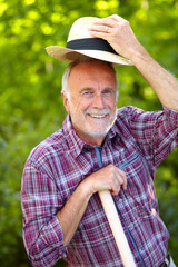 Senior gardener greets with hat