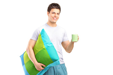 A smiling male holding a pillow and cup of coffee