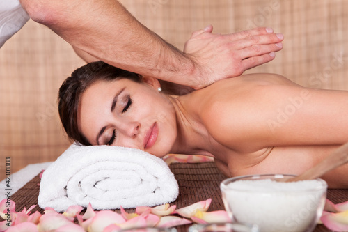 Beautiful young woman getting shoulder massage