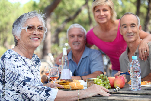 Senior woman having a picnic with friends