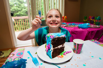 child with a giant piece of cake at her birthday party