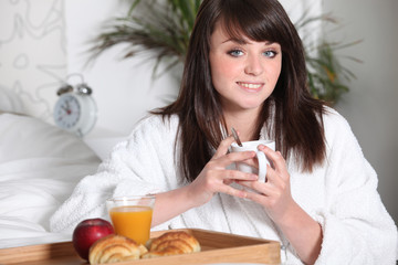 Teenage girl having breakfast in bed