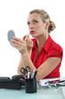 Blond secretary applying lip-stick at her desk