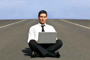 Man alone with laptop on airstrip