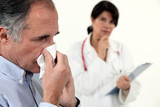Man blowing his nose next to a doctor