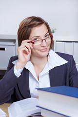 Geschäftsfrau schaut über Brillenrand