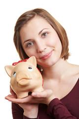 Frau hält Sparschwein auf Hand