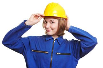 Frau im Arbeitsanzug setzt Helm auf