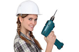 Smiling tradeswoman holding a power tool