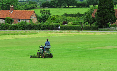 Man Mowing grass on an English Cricket field