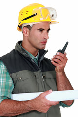 foreman with blueprints holding talkie walkie
