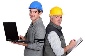 senior plumber and junior holding laptop and clipboard