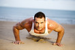 Man doing push ups on a beach