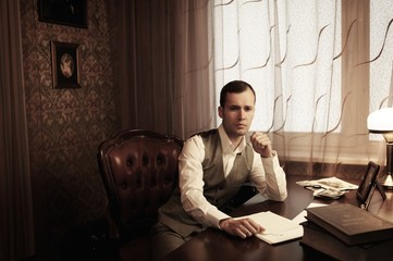 Pensive businessman in home interior behind table