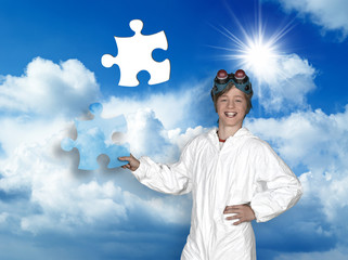 Young man holding a piece of puzzle against blue sky