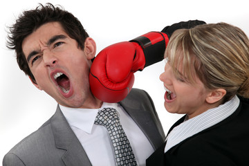 Woman punching her hard-headed colleague