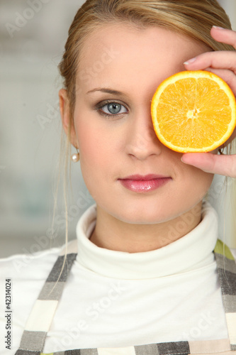 Woman covering her eye with orange slice