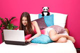 brunette teenager using a laptop in her room