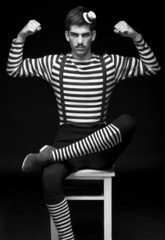 Morose circus performer sitting in a striped dress
