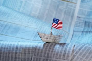 Papierschiff mit Flagge der USA auf Börsennachrichten