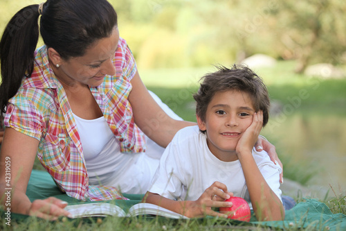 Mother and son lying on the grass