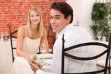 Couple in restaurant with present