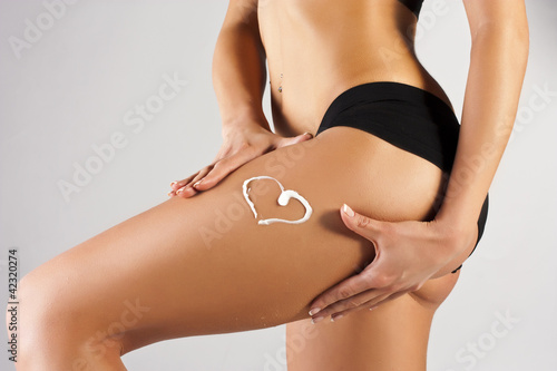 Woman applying moisturizer cream on legs. Perfect female figure
