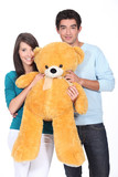 Young couple holding big toy bear