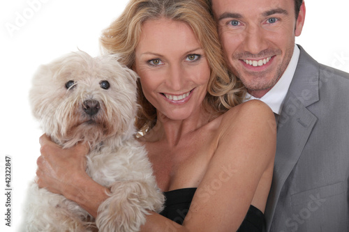 Couple holding dog.