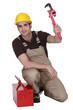 Man kneeling by tool box