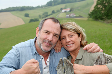 Senior couple leaning on fence in countryside