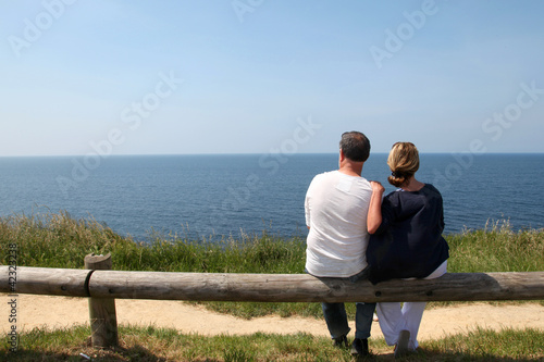 Couple sitting on fence enjoying panoramic sea view
