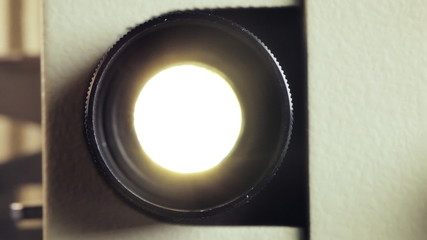 Front view of 8mm film projector lens in action.
