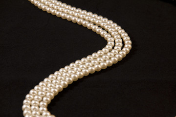 Necklace of pearls on black background