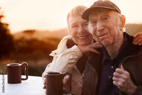 Cute senior couple in jackets outside at table smiling
