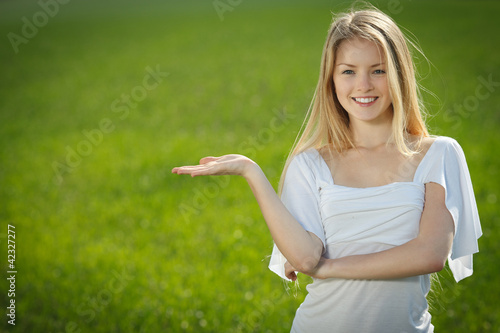 Closeup of smiling woman holding blank copy space on her palm