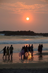 People taking a sunset stroll on Kovalam beach, Kerala, India