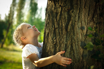 Little girl hugging a tree, looking up