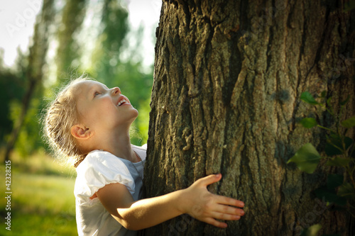 Leinwanddruck Bild Little girl hugging a tree, looking up
