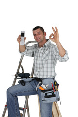 Carpenter with mobile giving the OK