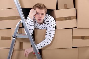 Man stuck behind stacks of cardboard boxes