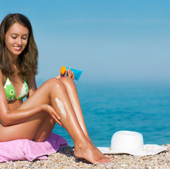 Tan woman applying sunscreen (focus on legs)