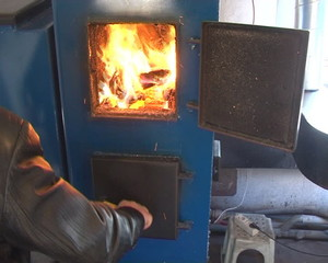 hand open boiler door. fire burning boiler fired pellets wood