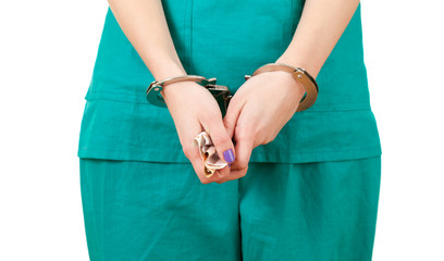 bribe in medicine - lady doctor with handcuffed hands with money