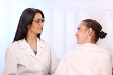 A doctor cosmetologist and a patient, indoors