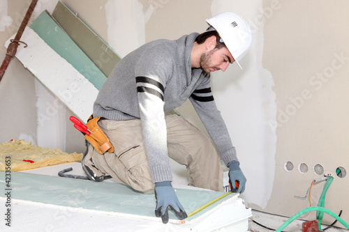 Bricklayer measuring plasterboard